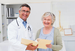 elder woman smiling with doctor beside